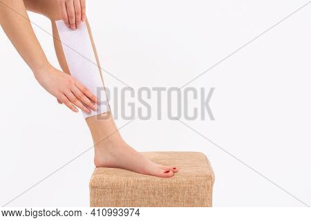 Woman Waxing Her Legs With Wax Tape At Home. Close-up Of Female Hand Waxing Her Leg With Wax Strip A