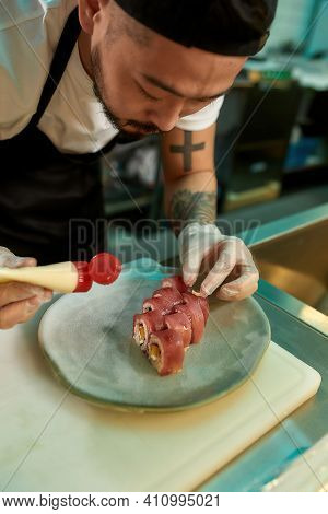 Professional Sushi Chef Carefully Adding Final Touch With Dedication To His Perfect Tuna Sushi. Japa