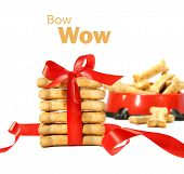 Dog biscuits wrapped with red bow on white background poster