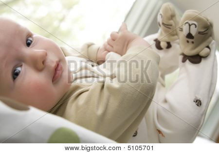 Baby Boy Lying On Back With Feet Up In The Air