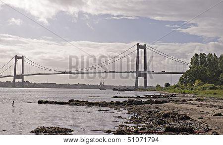 Sailboat Under Suspension Bridge
