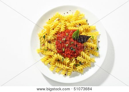 Looking down at a plate of cooked macaroni with sauce
