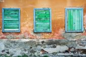 Three boarded up windows of an old rundown building. poster