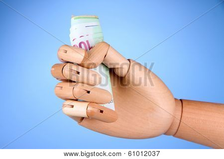 Money in wooden hand, on color background