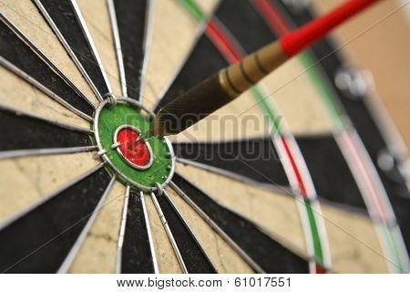 Dartboard with dart on bullseye