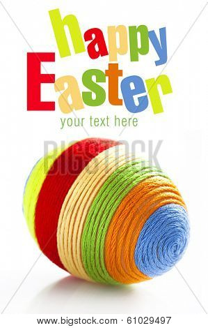Easter egg with colorful woolen yarn on white background. Space for text
