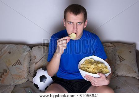 Supporter In Uniform Watching Football On Tv At Home And Eating Chips