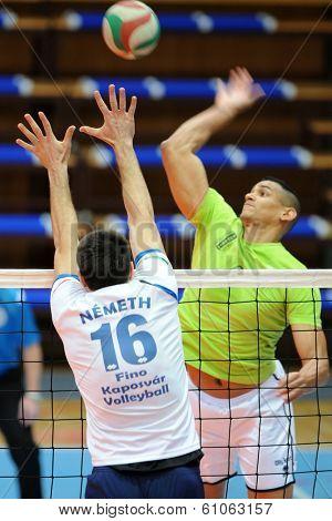KAPOSVAR, HUNGARY - FEBRUARY 25: Domotor Meszaros (R) in action at a Hungarian National Championship volleyball game Kaposvar (white) vs. Sumeg (green), February 25, 2014 in Kaposvar, Hungary.