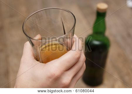 A Man Holding A Glass Of Scotch Next To A Bottle
