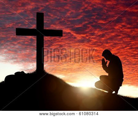 Silhouette of man praying to a cross with heavenly cloudscape sunset concept for religion, worship, love and spirituality