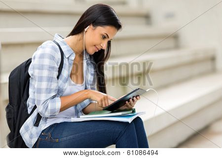 female university student using tablet computer listening music on campus