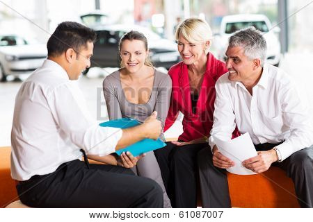 indian car dealer explaining sales contract to the family buying a car