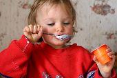 Little baby eating yogurt poster
