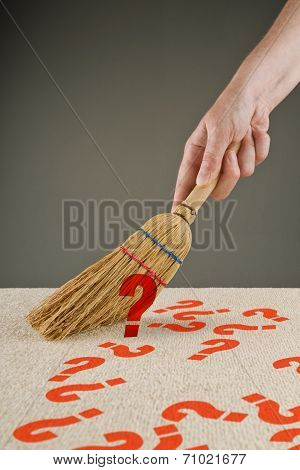 Hand Sweeping Question Marks From The Floor