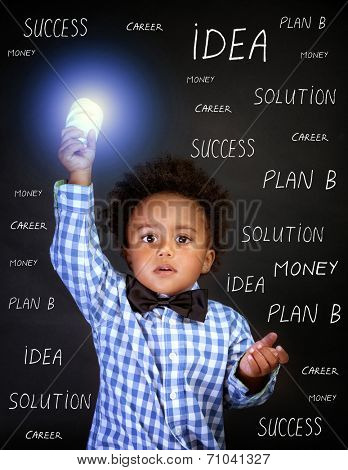 Portrait of little African genius boy with lightbulb in the hand on blackboard background, back to school, find solution concept