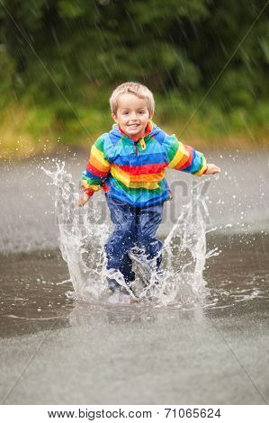 Boy jumping and splashing in rain puddle