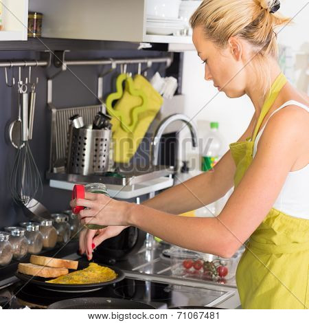 Young Mother Cooking at Home.