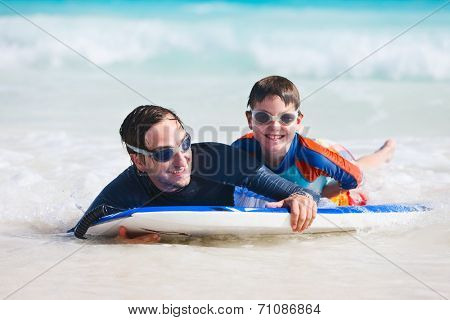 Father and son on vacation having fun surfing on boogie board