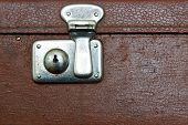 the closed metal rusty lock closeup on part of an old suitcase with the textured leather surface of dark brown color poster