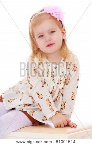 Adorable little girl sitting on the banquette.
