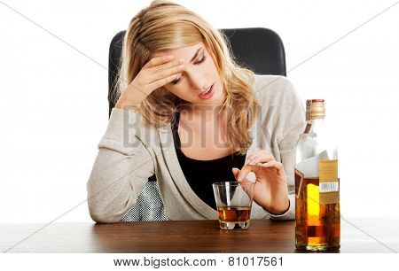 Yound beautiful woman in depression, drinking alcohol poster
