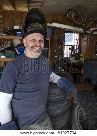 Man wearing welding helmet leaning against tires