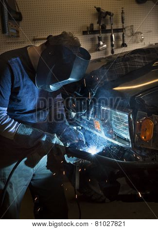 Man wearing welding helmet and welding the bumper of a vehicle poster