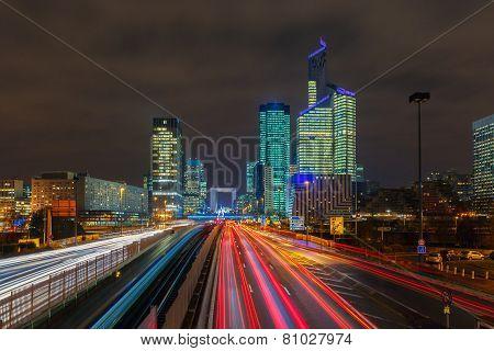 Night road with skyscrapers of La Defense, Paris, France.