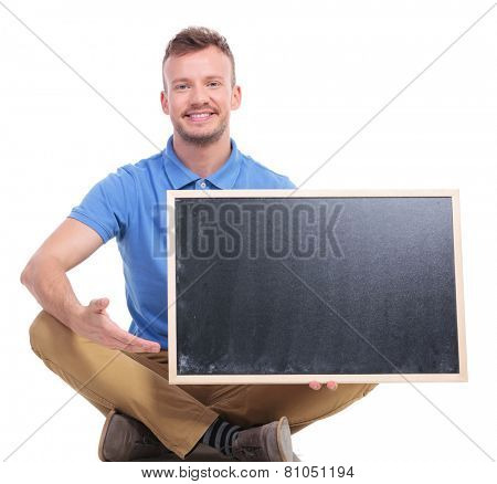 picture of a casual young man sitting on the floor with his feet crossed while holding a small blackboard and pointing at it. on a white background