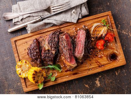 Sliced Medium Rare Grilled Beef Steak Ribeye With Corn And Cherry Tomatoes On Cutting Board On Woode