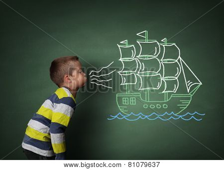 Child blowing a chalk drawing of a sailboat on a blackboard concept for wishing, dreams, hope and aspirations