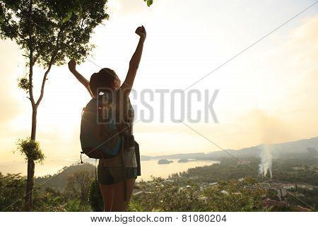 heering woman hiker open arms at mountain peak