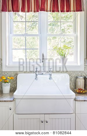 Kitchen interior with large rustic white porcelain sink and granite stone countertop under sunny window poster