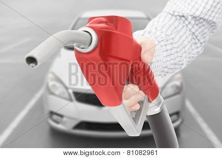 Red Color Fuel Pump Gun In Hand With Car On Background