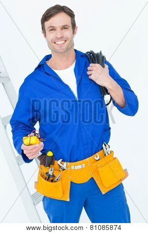 Portrait of happy electrician with wire roll and multimeter over white background