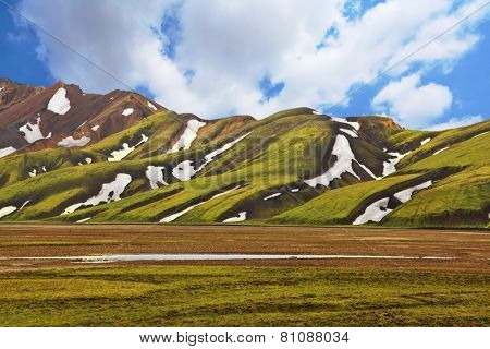 Magnificent colorful mountains. Reserve Landmannalaugar, Iceland. Green moss on smooth slopes and white spots snowfields in the gullies