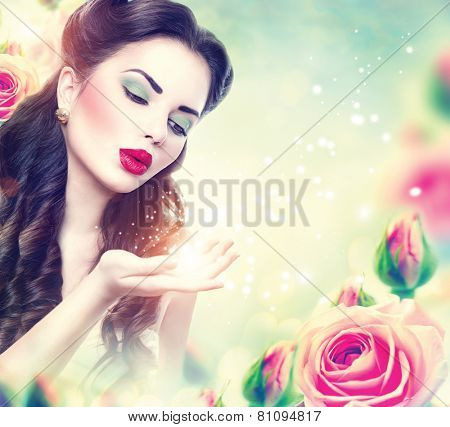 Retro woman portrait in beauty pink roses garden. Beautiful Vintage styled girl with flowers blowing magic stars in her hand. Perfect makeup and hairstyle. Gorgeous model lady. Luxury Make up and Hair