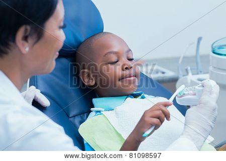 Female dentist teaching boy how to brush teeth in the dentists chair