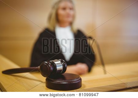 Serious judge with a gavel wearing robes in the court room
