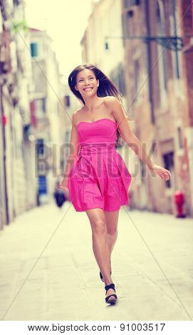 Summer dress. Happy beautiful woman in hot pink summer dress walking and running joyful smiling in Venice, Italy. Sexy fashion model girl in her 20s. Biracial Asian Caucasian female model outside.