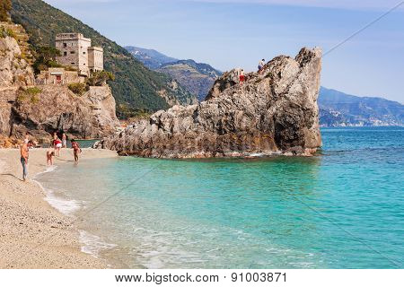 MONTEROSSO, ITALY - APRIL 12, 2015: Unidentified people relaxing on the beach of Monterosso in Italy. Monterosso is one of five famous coastline villages in the Cinque Terre National Park.