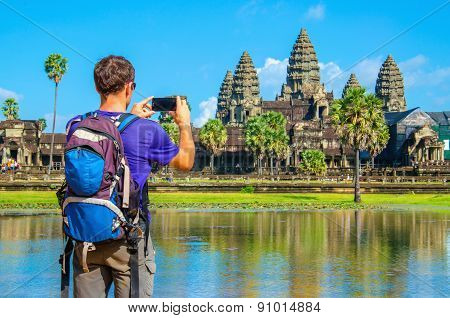 Young man taking photo of Angkor Wat, Cambodia