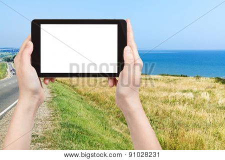 travel concept - tourist photograph coastline of Sea of Azov in resort village Golubitskaya on Taman Peninsula Russia on tablet pc with cut out screen with blank place for advertising logo poster