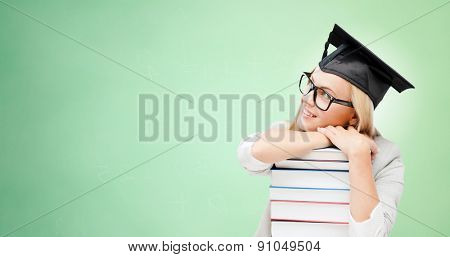 education, happiness, graduation and people concept - picture of happy student in mortar board cap with stack of books daydreaming over green background