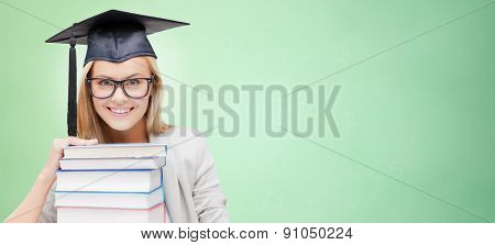 education, happiness, graduation and people concept - picture of happy student in mortar board cap with stack of books over green background