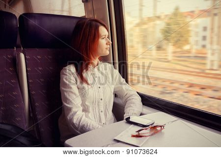 Young woman traveling with train  looking out the window while sitting