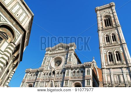 Florence Cathedral of Santa Maria del Fiore or Duomo di Firenze in Gothic style detail of the facade Brunelleschi's dome and Giotto's bell tower against the blue sky. Florence Tuscany Italy.