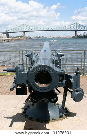 Jacques Cartier Bridge and Saint Lawrence River view from behind a gun at the base of Montreal Clock Tower