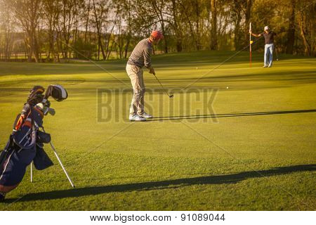 Two male senior golf player putting on green at twilight, with golf bag in foreground.
