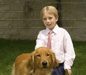 a little boy with his best friend a golden retriever pose for a photograph. poster